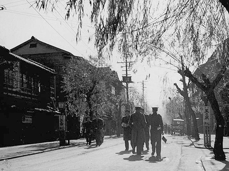 1945年(昭和20年)/二日市湯町/湯町を歩く米軍兵。右奥に大賀酒造の「玉出泉」の看板があります。